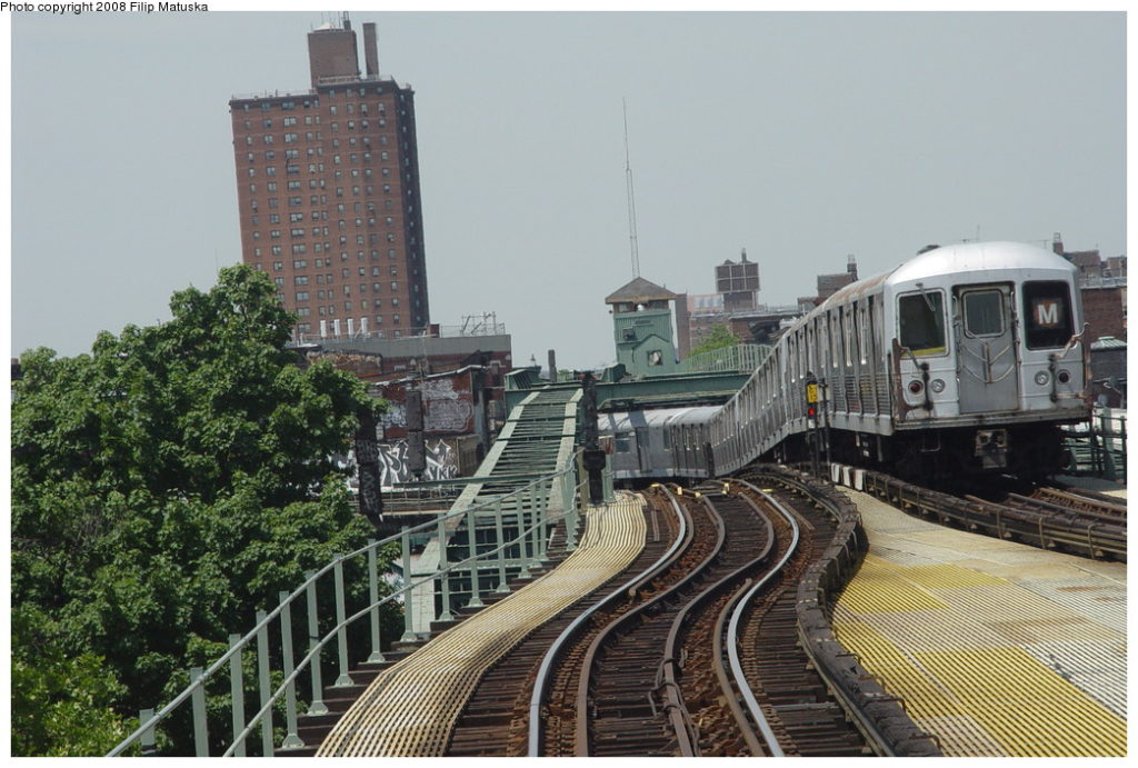M train passes by the abandoned upper level at Myrtle Ave.  Photo by Filip Matuska via nycsubway.org
