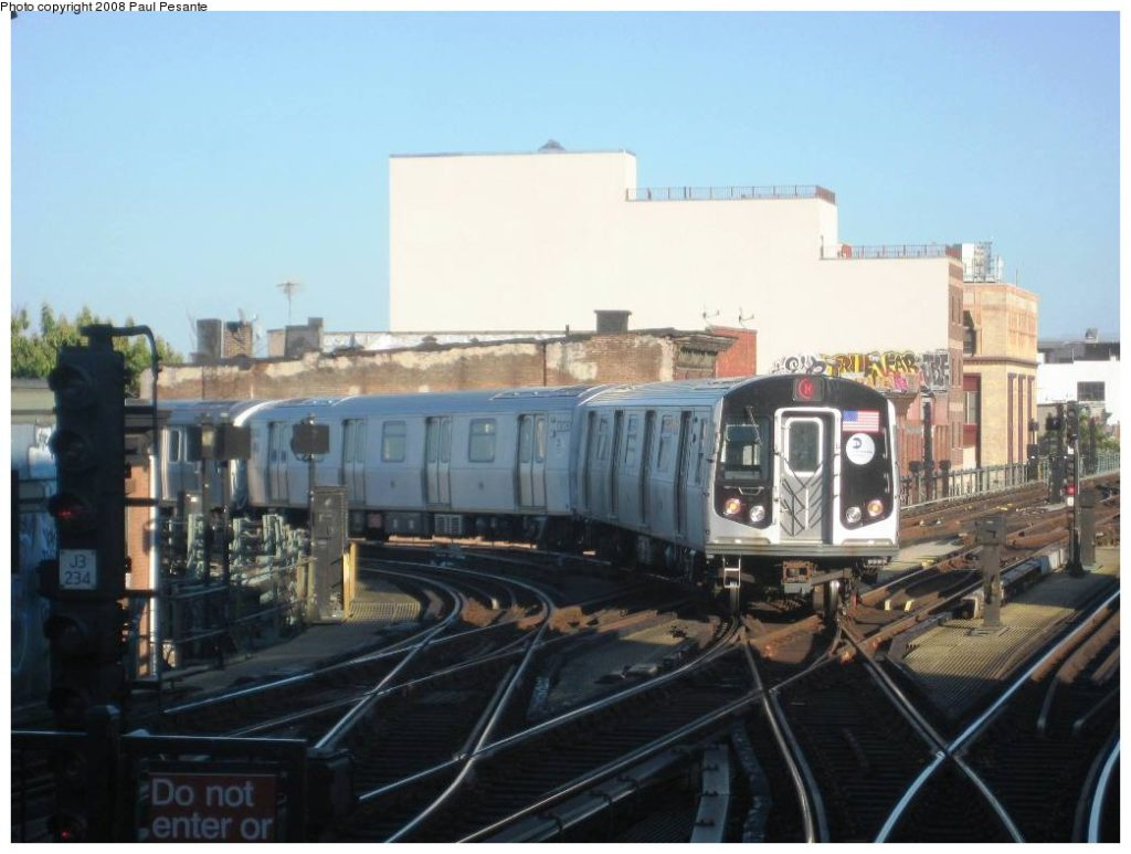 An M train passes at grade over the J train track causing delays.  Photo by Paul Pesante via nycsubway.org